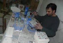 Craftsman painting ceramic tiles.