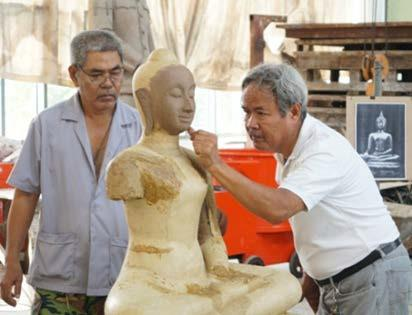 The sculptor, Master Kongket, is applying wax to the surface of the clay body in order to finish the detail decoration especially the face of the Buddha image.