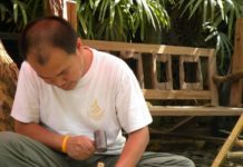 The artisan of Ban Thawai is working on wood and a completed piece of wood art with natural look.